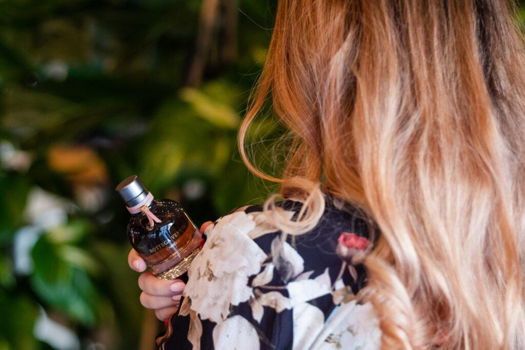 Dziewczyna trzymająca buteleczkę perfum bottega veneta