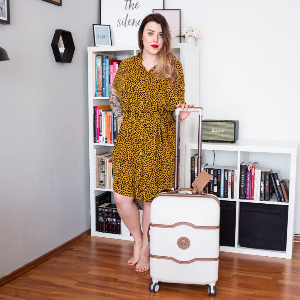 dziewczyna w sukience w panterke z walizką chatlet air