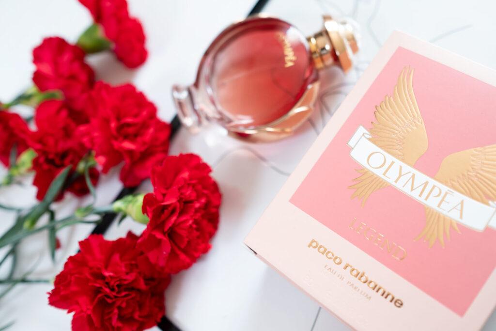 Zapach Olympéa Legend opakowanie wśród kwiatów