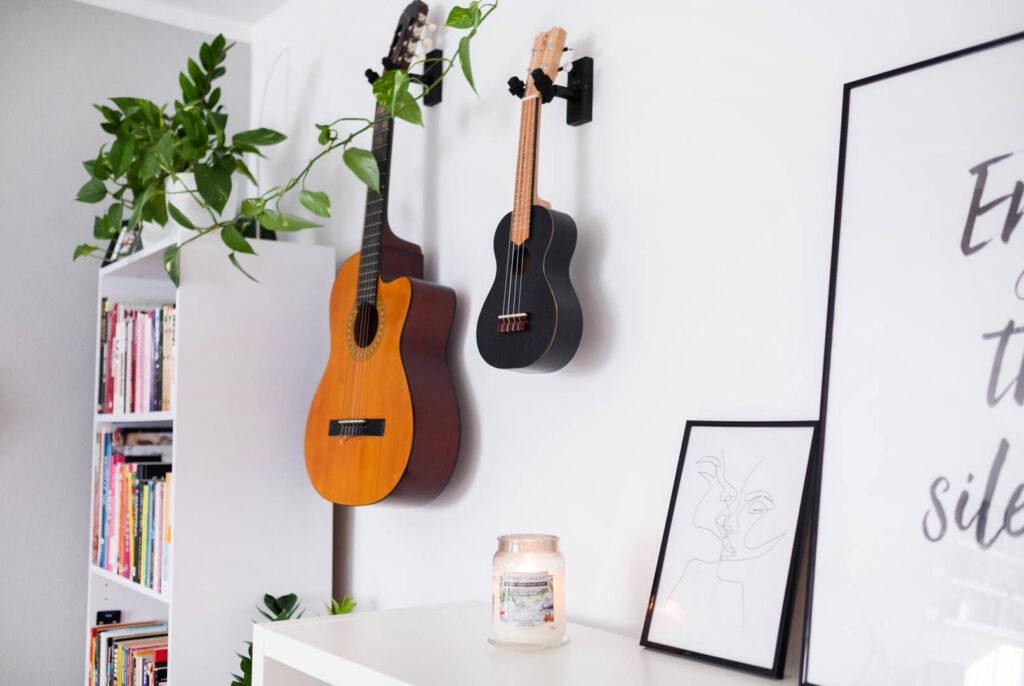 jesieniara pali świece zapachowe w pokiju z gitarą ukulele i książkami