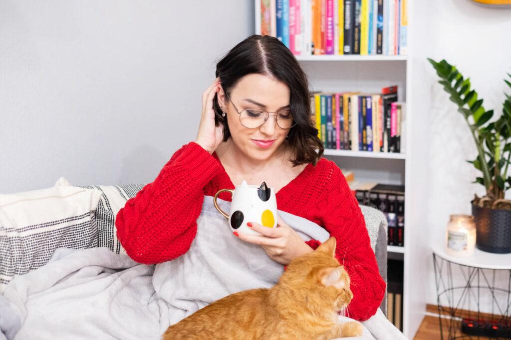 Dziewczyna w czerwonym swetrze jesieniara pod kocem z rudym kotem i herbatą